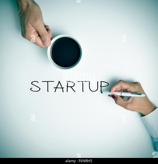 high-angle shot of a young man with a cup of coffee and a young woman writing the text startup with a pen - Stock-Bilder