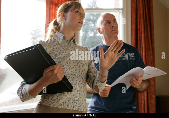 female estate agent looking at house with male client - Stock Image