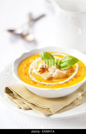 Pumpkin soup with croutons and basil - Stock Image