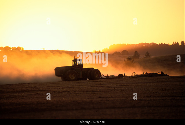 Oregon agriculture.  Farm with tractor plowing field at sunset. - Stock Image