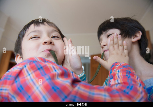 Brothers eating gummy snake - Stock Image