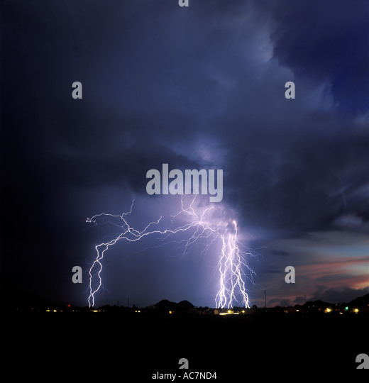 Lightning strikes over a city dotted with glowing lights from a dark blue stormy sky in Southern Arizona during - Stock Image