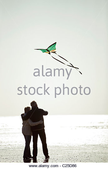 A senior couple flying a kite on the beach, rear view - Stock Image