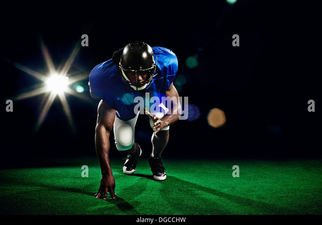 American football player crouching - Stock Image