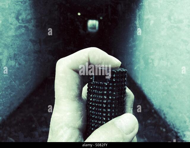 Turning on pepper spray before walking down a tunnel under a highway in California. - Stock Image