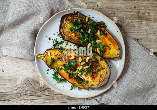 Roast aubergine with  crispy kale and pine nuts - Stock Image