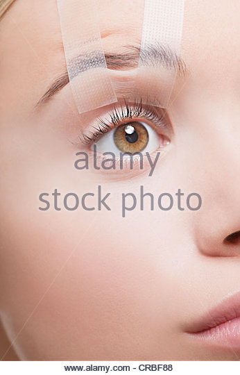 Close up of woman's eye taped open - Stock Image