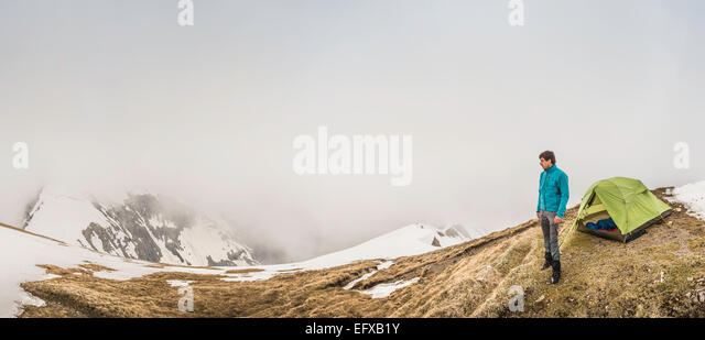Panoramic of young man and tent in mist, Bavarian Alps, Oberstdorf, Bavaria, Germany - Stock Image