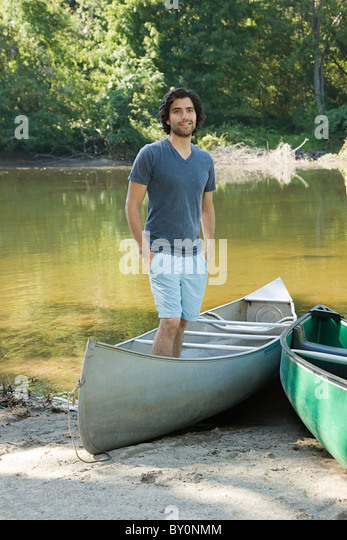 Young man standing in rowboat - Stock Image