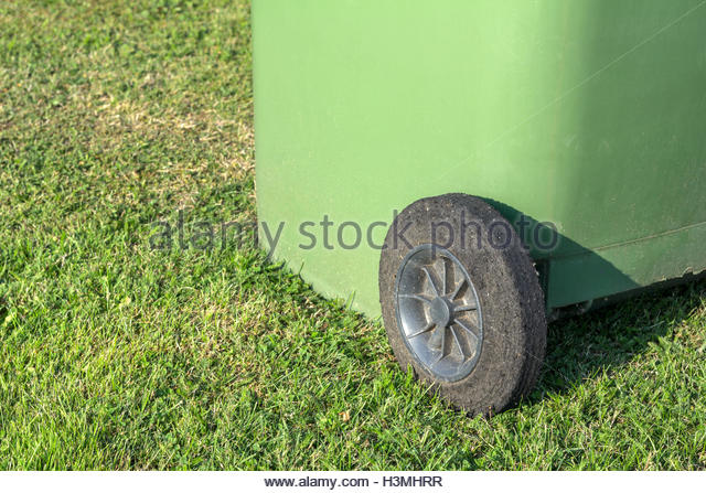 Green recycling wheelie bin placed on grass - Stock Image