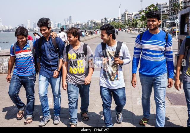 Mumbai India Asian Churchgate Marine Drive Back Bay Arabian Sea student teen boy man friends walking - Stock Image