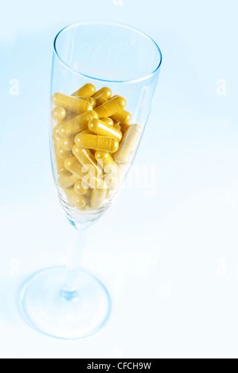 Conceptual image about the risk of taking pills with alcohol. Blue background. - Stock Image