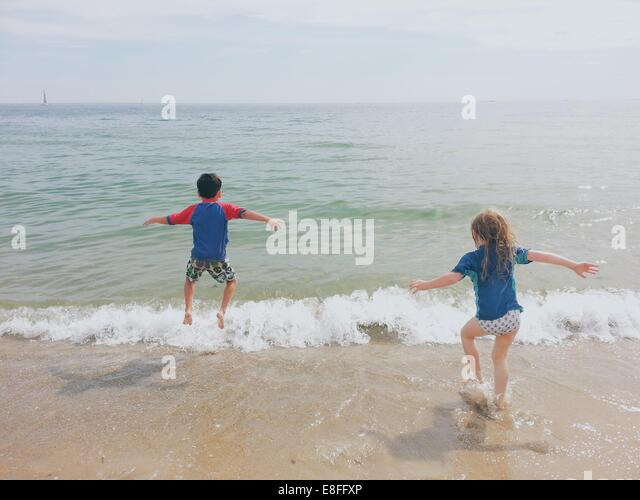 Boy and girl running into the ocean - Stock Image