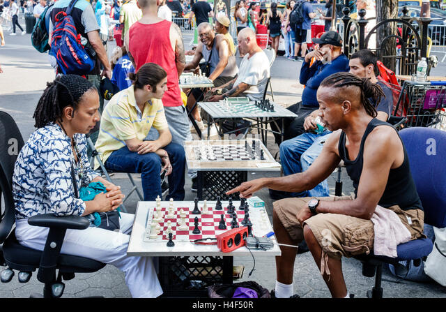New York New York City NYC Manhattan Stuyvesant Square public park Black man woman chess game board crate chairs - Stock Image