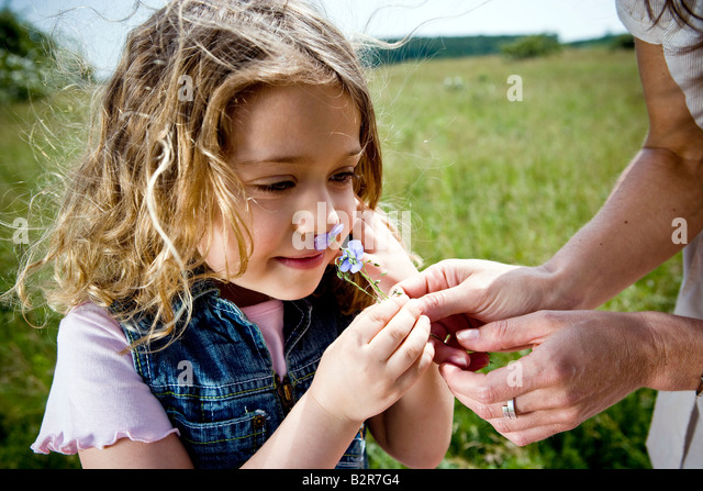 Girl smelling flower - Stock Image