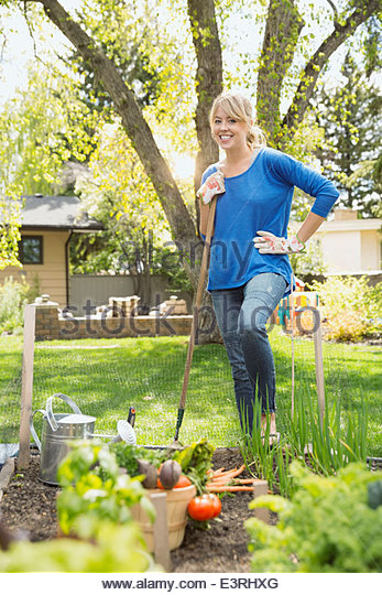Portrait of woman with hoe in vegetable garden - Stock Image