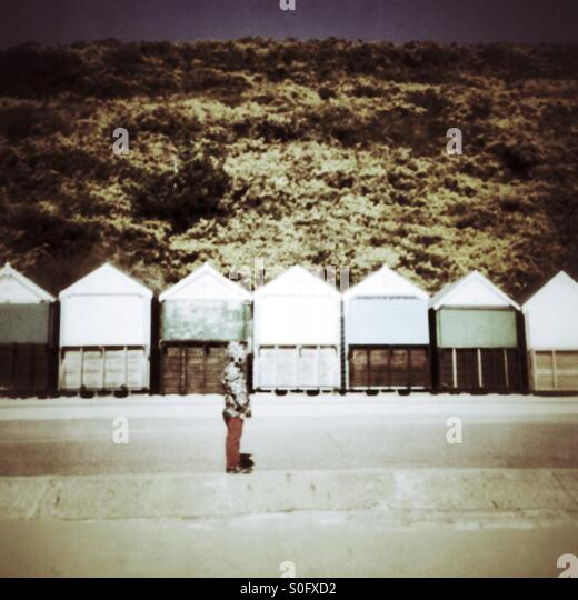 Child standing in front of beach huts - Stock Image