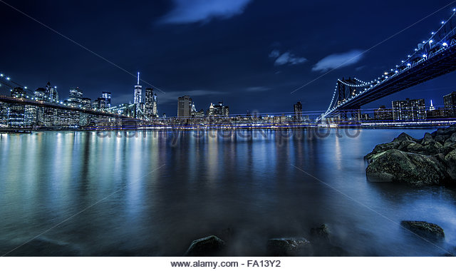 View of New York City or Manhattan Skyline and Brooklyn Bridge from the Brooklyn Promenade at night with water reflections - Stock Image