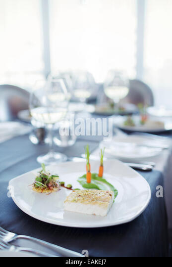 Fancy fish meal on plate in restaurant - Stock Image