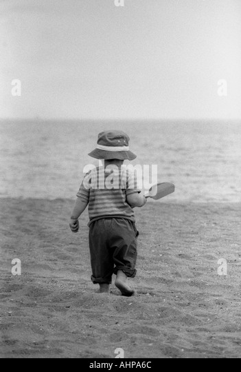 Small boy walking on beach with hat on and shovel in hand - Stock Image