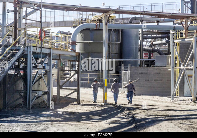3 miners with picks on road through massive tangle of pipes vats conveyor belts abutting copper mill at mission - Stock Image