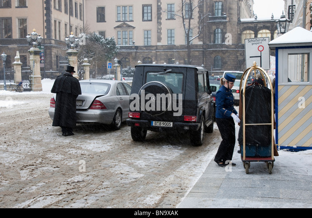 Hotel staff looking after departing guest in winter, Dresden, Germany. - Stock Image