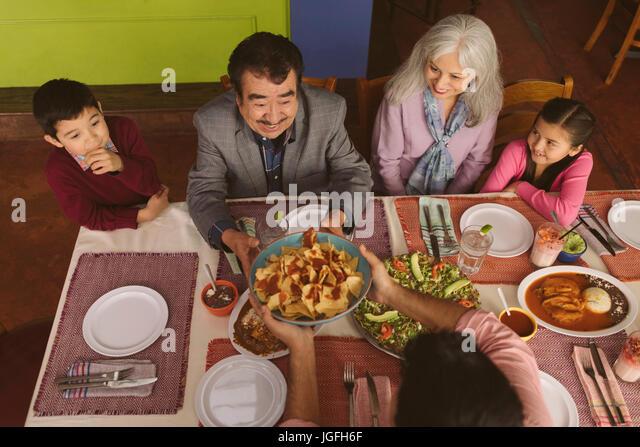 High angle view of family enjoying dinner in restaurant - Stock Image