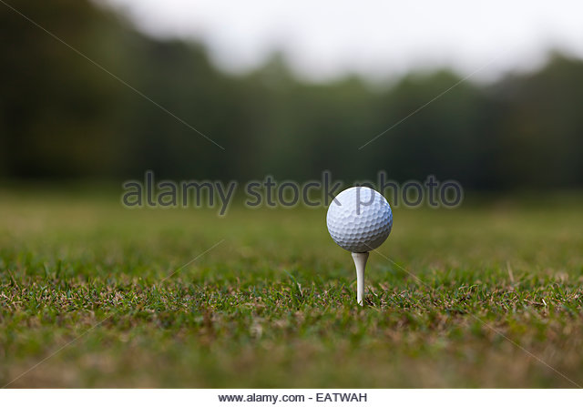 A golf ball on a tee at a driving range. - Stock Image
