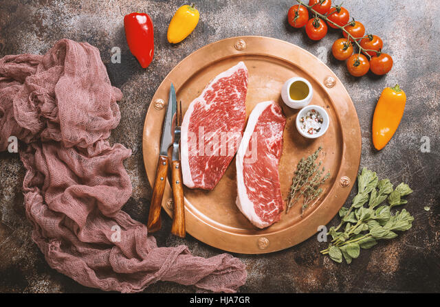 Fresh raw Prime Black Angus beef strip steaks on metal plate over dark rustic concrete background, top view. Ingredients - Stock Image