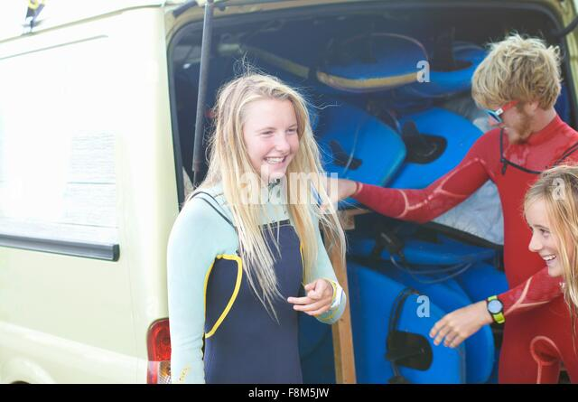 Group of surfers standing beside van, getting ready to surf - Stock Image