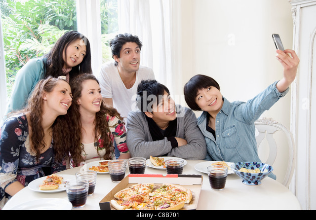 Happy friends taking photograph - Stock Image