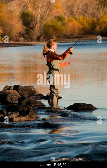 Idaho, Boise, Woman fly fishing on the Boise River with autumn colors. - Stock Image