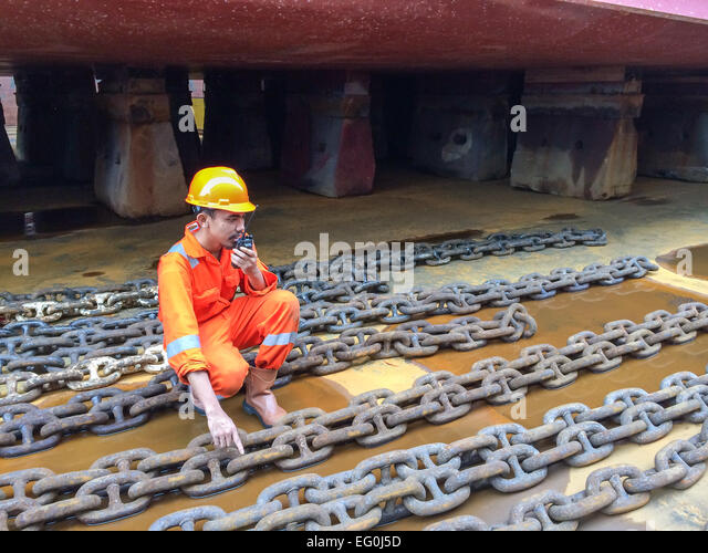 Dock worker in a shipyard talking on a walkie talkie - Stock Image