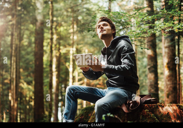 Young handsome man sitting in the woods and using a digital touch screen tablet, wi-fi connection and freedom concept - Stock-Bilder