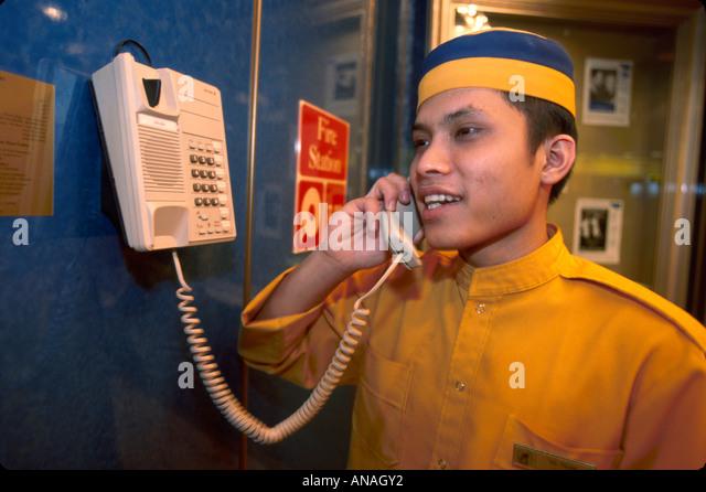 Bahamas Atlantic Ocean Holland America Line ms Maasdam cruise ship Asian porter telephone man male uniform - Stock Image