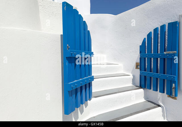 A blue gated entrance to a traditional white painted building in Oia, on the Greek island of Santorini - Stock Image