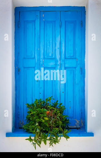 Window shutter in characteristic blue on white colors in Kokkari on the Greek Island of Samos. - Stock Image