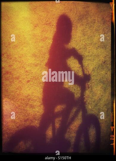 The shadow of a 4 year old girl riding her bicycle is cast onto a field of green grass. The colours are distorted - Stock-Bilder
