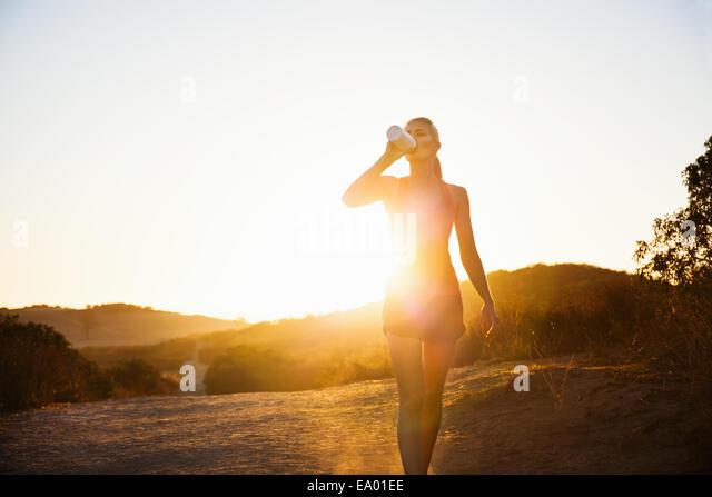 Female jogger drinking in sunlight, Poway, CA, USA - Stock Image
