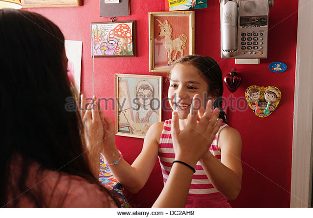 Girls playing hand clapping game at home - Stock-Bilder