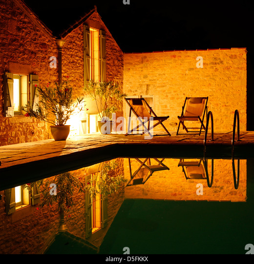 Reflection in a swimming pool at night, France - Stock Image