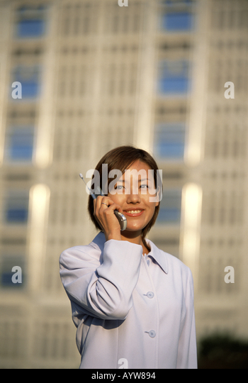 Woman talking on a cell phone with tall office building in the background - Stock-Bilder