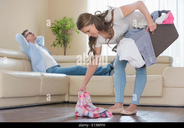 Woman with laundry basket picking clothes while man relaxing on sofa in background - Stock Image