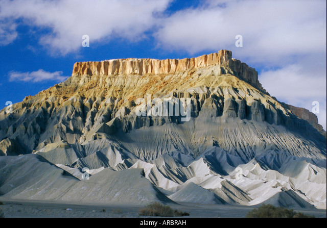 Mesaverde Sandstone cliff over gullied slopes of grey Mancos Shale, resulting from river erosion, Hanksville, Utah, - Stock Image