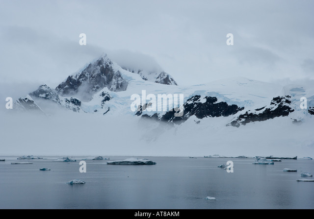 Antarctic scene of a mountain peaking through the mist in a calm antarctic bay dotted with icebergs - Stock Image