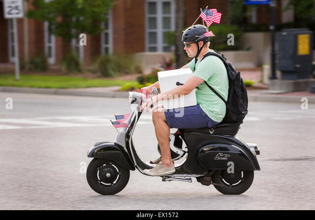 A man carrying a cooler on his scooter rides decorated with American flags during the Daniel Island Independence - Stock Image