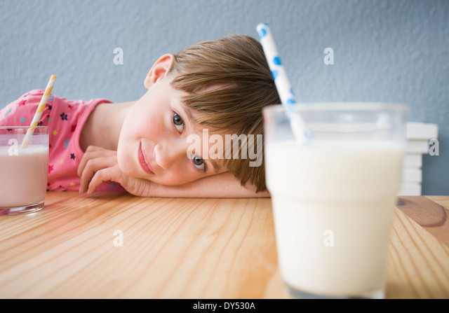 Girl looking at glass of milk - Stock Image