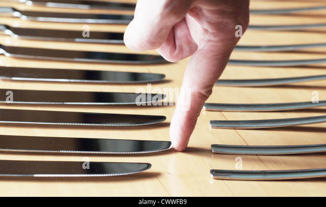 Fingertip touching point of butter knife - Stock Image