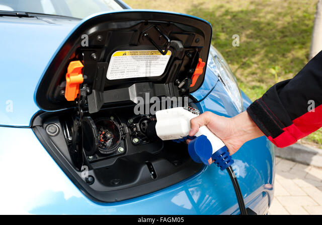 Charging point with plug and power cord for electric and hybrid cars. Focused on the plug - Stock Image