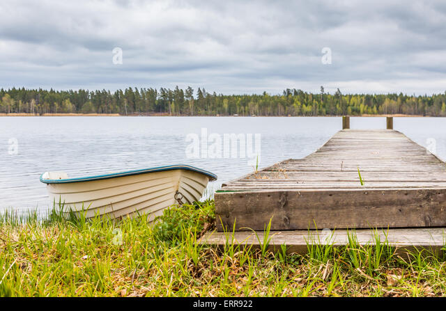 White Rowing Boat Next to Wooden Pier with a Cloudy Grey and White Sky in the Background - Stock Image